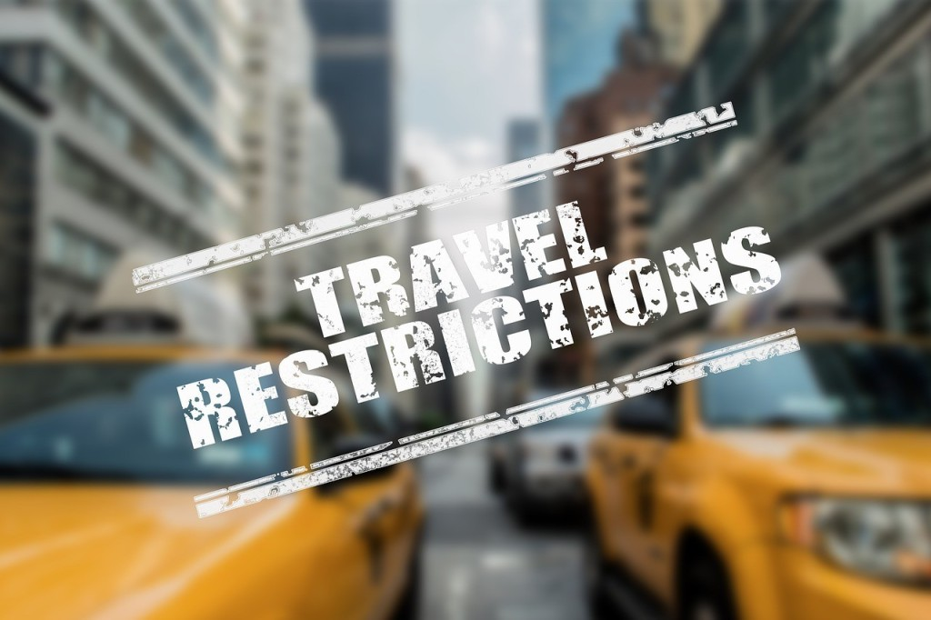 TRAVEL RESTRICTIONS written over a busy street in NYC