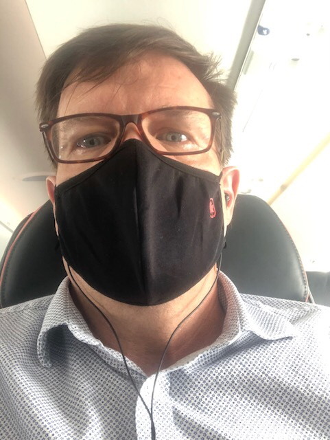 Selfie of the Author wearing a mask while flying on the plane