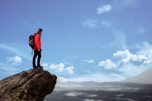A person standing on the top of a cliff looking at a distance.