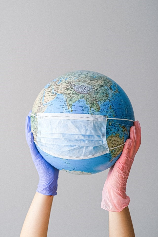 Hands holding a mask on a globe