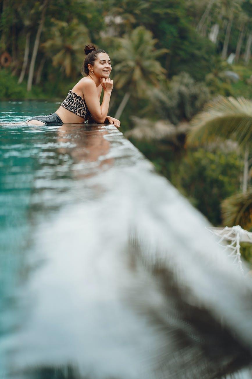 happy woman resting in pool in tropical resort