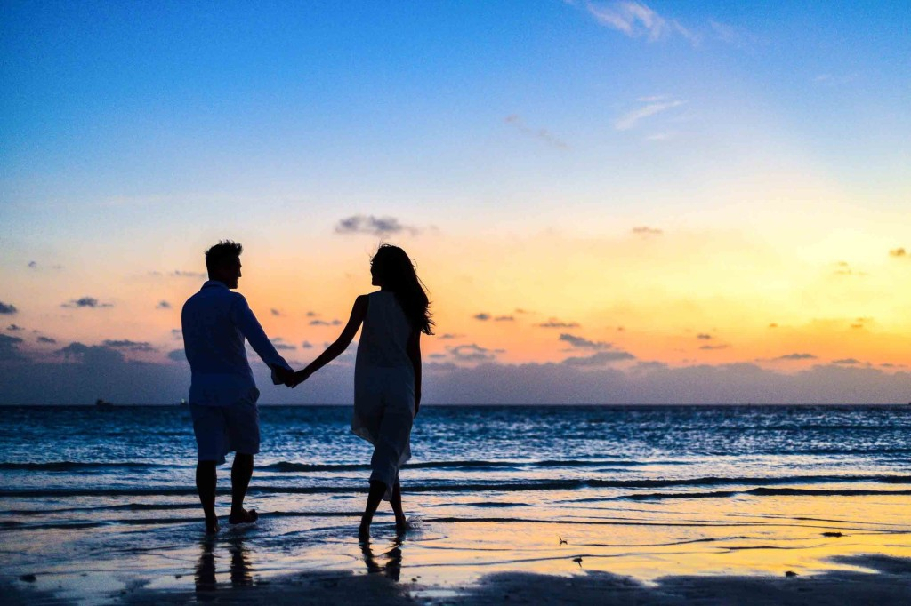 A couple holding hands on the beach at sunset