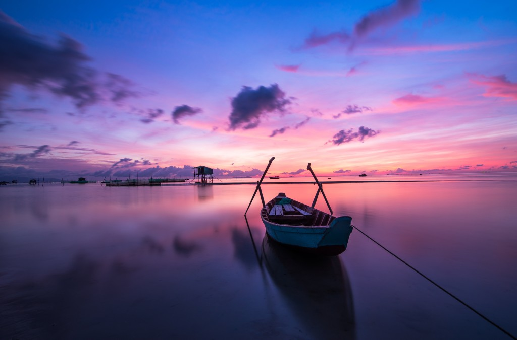 A boat on the calm water at sunset
