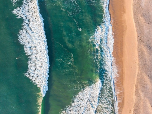 birds view of a beach and waves