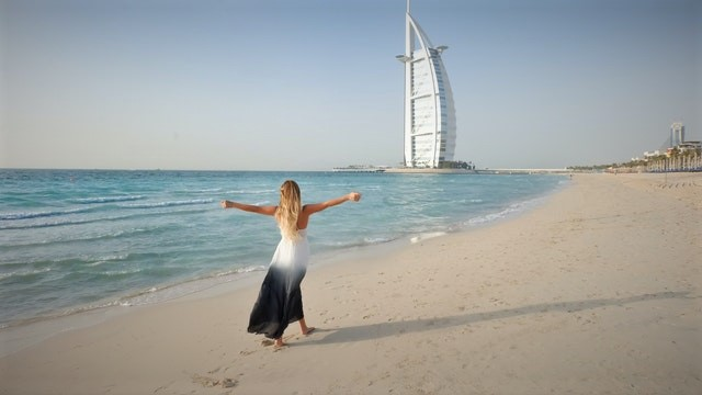 a woman walking on a Dubai beach