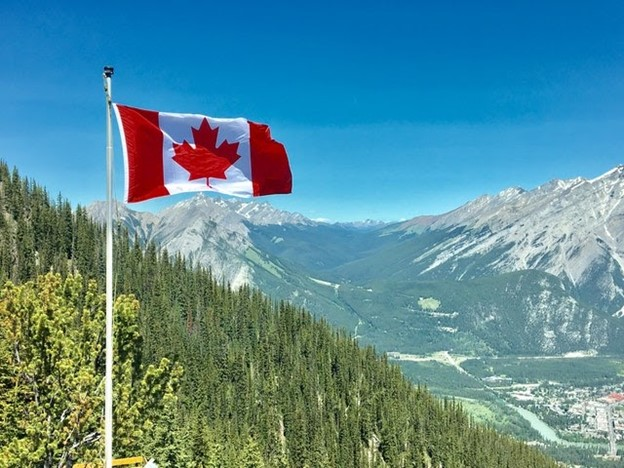 a Canadian flag and mountain ranges