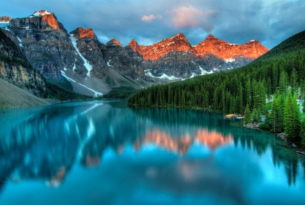 a big lake at the foot of mountains in Canada, symbolizing the best places to experience the true spirit of Canada
