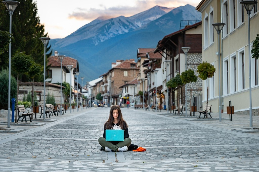 A woman working on a laptop in the middle of a street