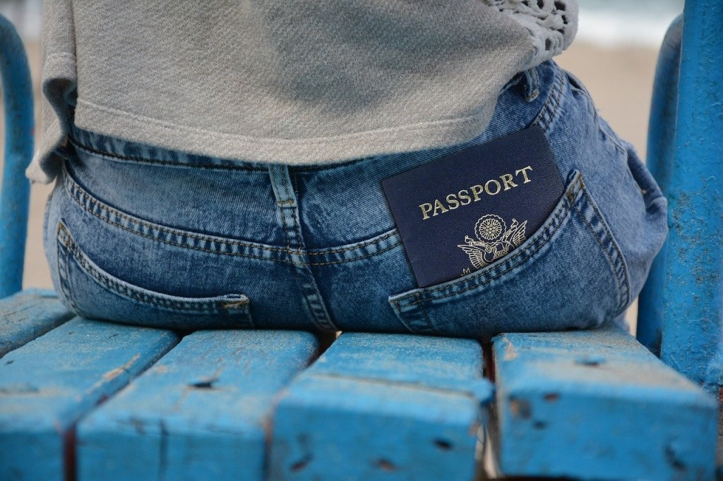Woman sitting on a bench with a passport in her pocket