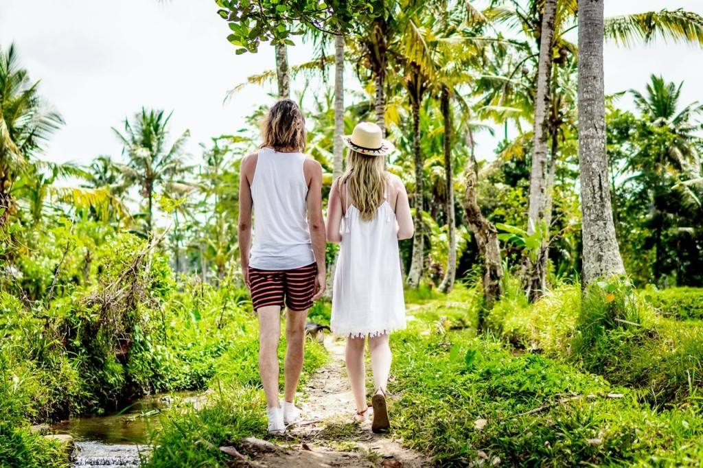 Man and woman walking towards palm trees
