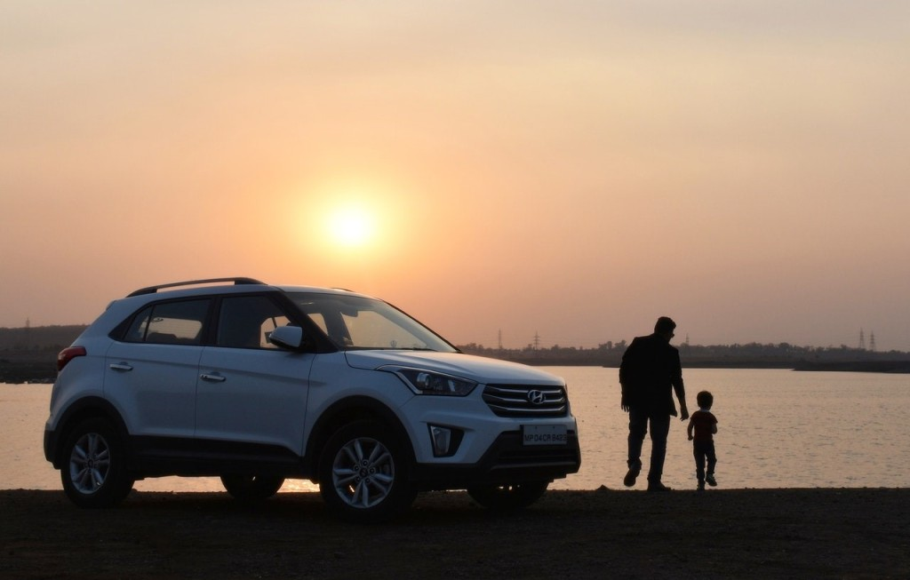 A man and a child near white SUV during sunset