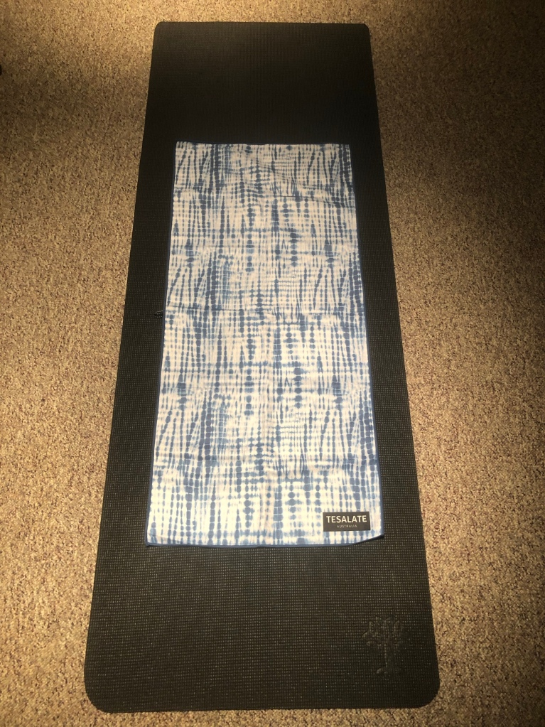 A Tesalate workout towel on a yoga mat