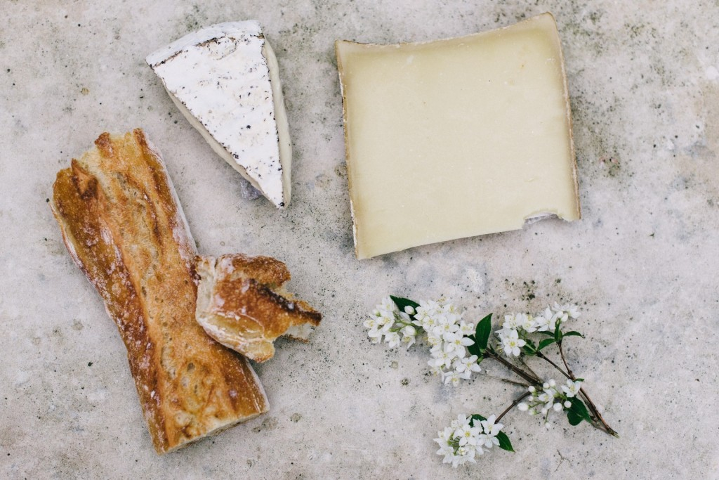 Two wedges of cheese next to a flower and a pastry.