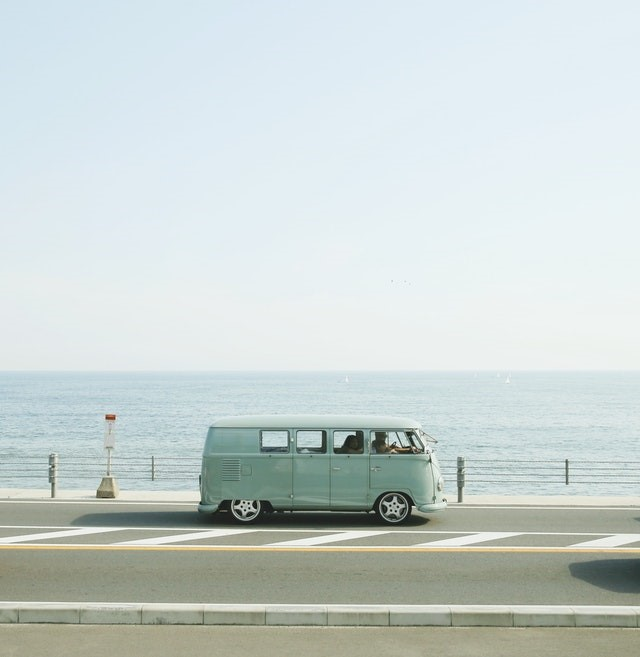 A blue van driving on a road